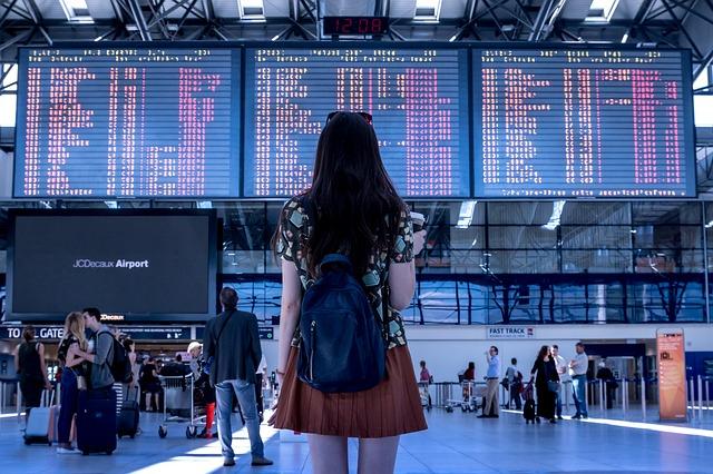 mladá žena zjišťuje časové údaje o odletech příletech