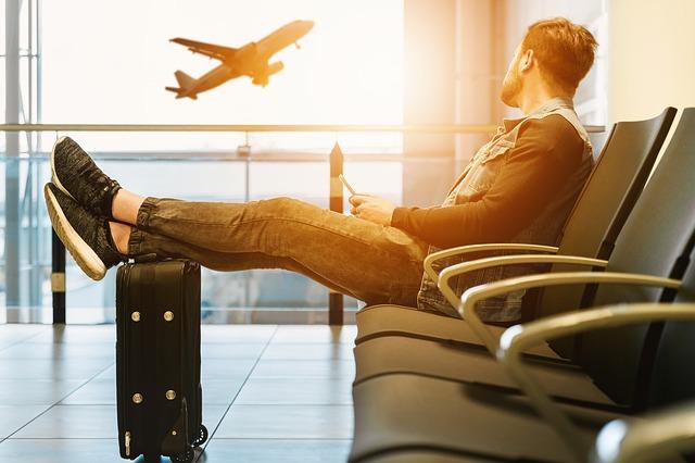 samotný muž v letištní hale smutně sleduje odlet letadla